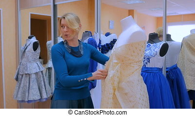 Fashion designer working with new model tailoring dress on...