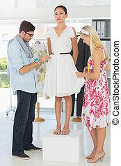 Fashion designers adjusting dress on model