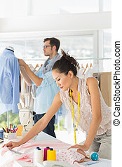 Fashion designers at work in bright studio