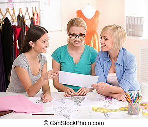 Fashion designers at work. Three cheerful young women ...