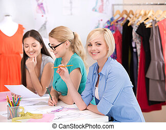 Fashion designers at work. Three cheerful young women working at fashion design studio
