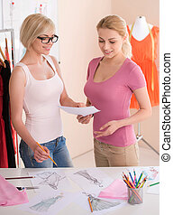 Fashion designers at work. Two cheerful young women working at fashion design studio