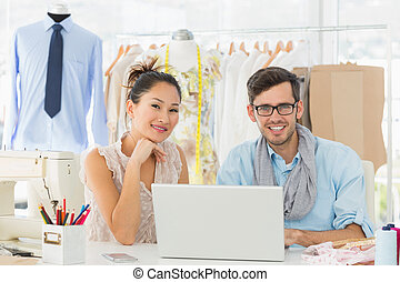 Fashion designers using laptop in studio - Male and female ...