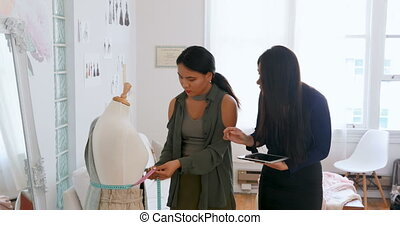 Fashion designers using tablet while measuring dress makers...