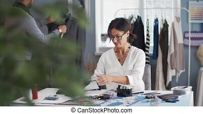 Beautiful woman in eyeglasses sitting at desk with garment accessory while bearded man adjusting jacket on mannequin. Concept of tailoring and designing.