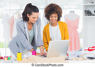 Fashion designers working on a laptop in a creative office