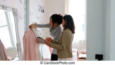 Fashion designers working together on dressmakers model 4k -...