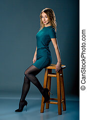 Fashion Dressed Girl Sitting on Chair. Full length Portrait. Beauty Woman on dark background.