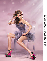 Fashion Dressed Sexy Girl Sitting on Chair. Woman in Purple Dress and High pink Heels