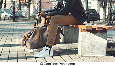 Fashion elegant african man with bag sits on the bench in the park close up