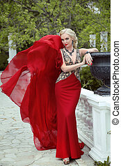 Fashion elegant blond woman model in red gown with blowing fabric. Outdoor full length portrait photo.