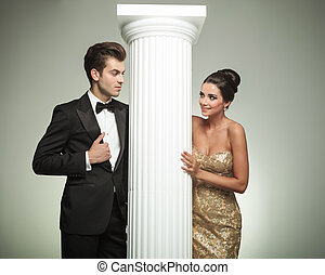 fashion elegant  couple looking at each other near column