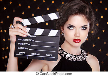 Fashion elegant woman with sexy red lips holding cinema...