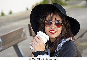 fashion girl drinking coffee on the street