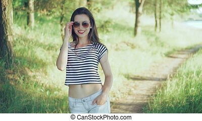 Fashion girl flirting, posing and looking on a camera in the park. 4k