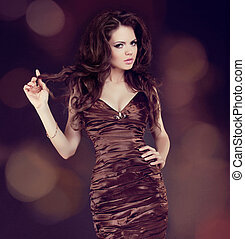 Fashion girl model, brunette woman with shiny curly silky hair in elegant dress
