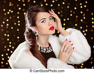 Fashion girl model posing in white fur coat. and luxury jewelry. Winter portrait of lady on golden holiday lights background.