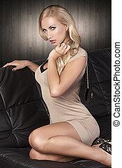 fashion girl sitting on a black sofa