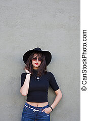 fashion girl with hat on the wall