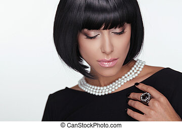 Fashion Haircut. Makeup. Sexy Lady. Stylish Fringe. Short Hair Style. Brunette woman with jewelry pearls.