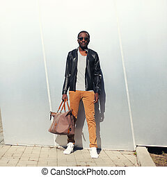 Fashion handsome african man model wearing a sunglasses and black leather jacket with bag in city
