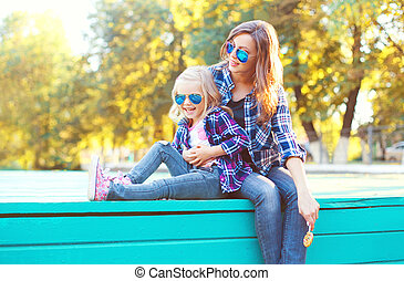 Fashion happy mother with child daughter having fun together in the park