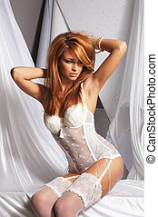 Fashion image of young and sexy redhead woman in white...