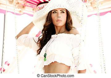 fashion girl in summer outfit and hat pose at carousel in amusement park