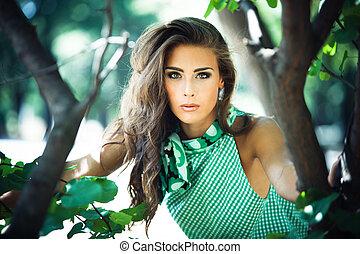 fashion in wood - young woman in green dress fashion shot in...