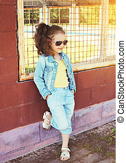Fashion kid concept - portrait of stylish little girl child wearing a jeans clothes and sunglasses posing outdoors