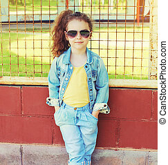 Fashion kid concept - stylish little girl child wearing a jeans clothes and sunglasses outdoors in the city