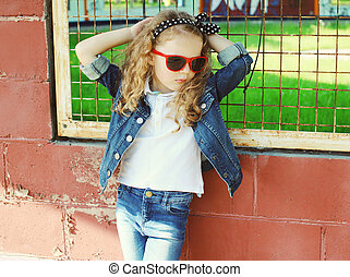 Fashion kid concept - stylish little girl child wearing a jeans clothes and sunglasses posing in the city