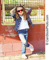 Fashion kid concept - stylish little girl child wearing a jeans clothes and sunglasses posing summer in the city
