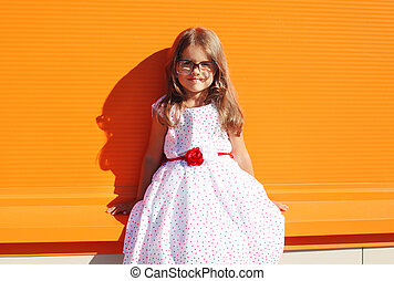 Fashion kid, portrait of beautiful little girl in white dress against the bright wall