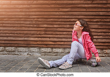 Stylish little girl child wearing a summer or autumn pink jacket, white jeans, sunglasses
