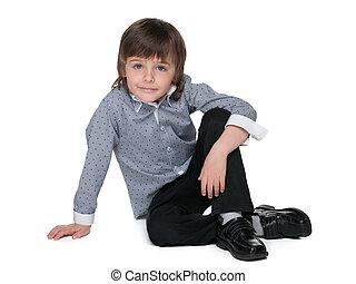 Fashion little boy sits on the floor