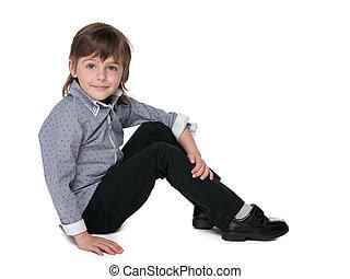 Fashion little boy sitting on the floor