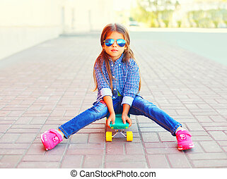 Fashion little girl child sitting on skateboard in the city