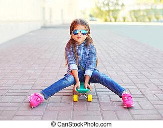 Fashion little girl child sitting on skateboard in city
