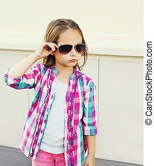 Fashion little girl child wearing a pink checkered shirt and sunglasses in city