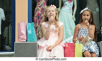 Fashion little girls in summer dresses eating ice cream in front of clothing store