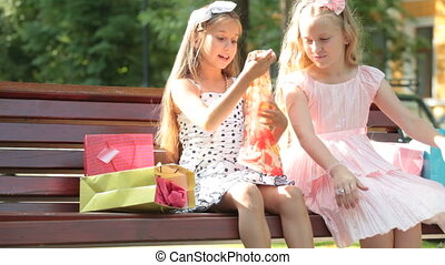 Fashion little girls in summer dresses having fun on a bench