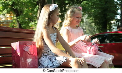 Fashion little girls sitting on a bench in the summer