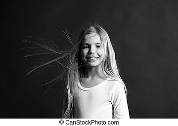 Fashion, look hairstyle. Child model smiling with blowing long hair. Girl with adorable smile on dark background. Happy childhood concept. Beauty and hairdressing salon.