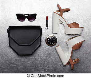Fashion luxury female set, black handbag clutch, sunglasses, shoes heels, lipstick and little pocket mirror over textured silver background, flat lay