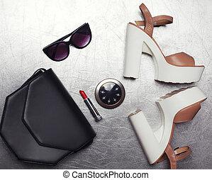 Fashion luxury female set, black handbag clutch, sunglasses, shoes heels, lipstick and little pocket mirror on textured silver background, flat lay