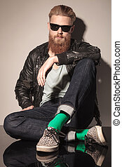 Fashion male model in leather jacket sitting
