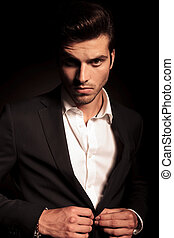 fashion man buttoning his suit on black background