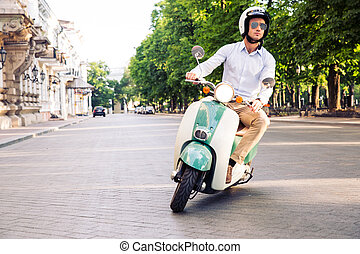 Fashion man driving a scooter in helmet in old town