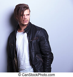 fashion man in leather jacket looks away